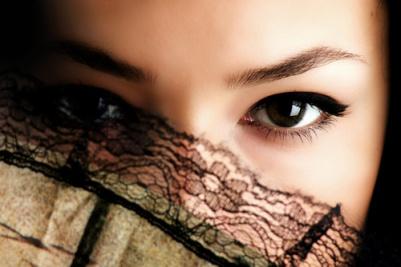 female eyes behind fan