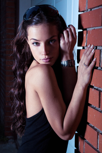night portrait outside, model is leaned on the wall